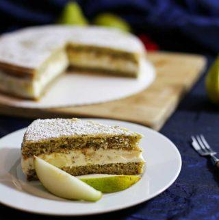 Ein Stück Ricotta-Birnen-Torte auf einem Teller, garniert mit zwei Birnenspalten. Im Hintergrund der Rest der Torte.