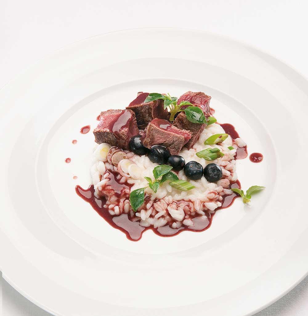 Ein Teller mit Risotto mit Frühlingszwiebel, Kastanien und Reh, mit Heidelbeeren und Kräutern verziert.