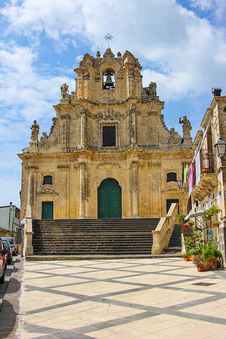 Die Barockkirche Chiesa Made, zu der eine Treppe hinaufführt, an der Seite der Straße parken Autos.