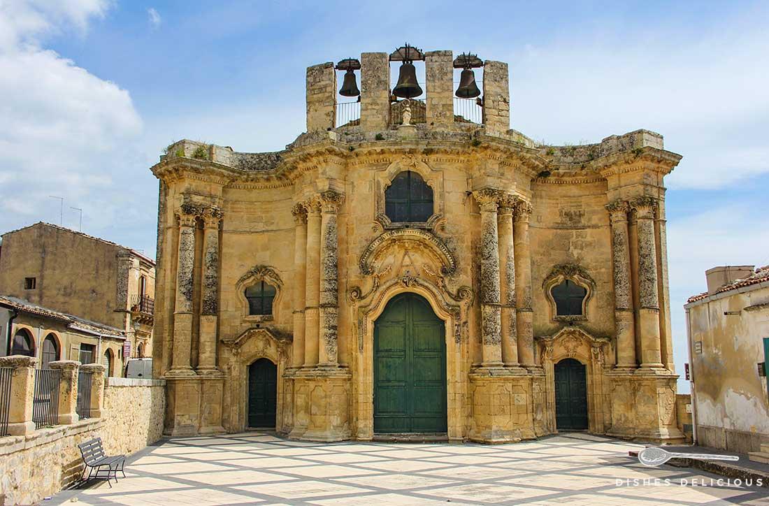 Die kleine, kastenförmige Chiesa Sant'Antonio in Buscemi mit drei offen befestigten Glocken auf dem Dach. Auf dem Vorplatz steht eine Bank.