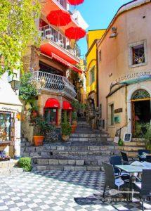 Der kleine Piazza Duomo in Castelmola mit der mit roten Schirmen dekorierten Bar Turrisi.