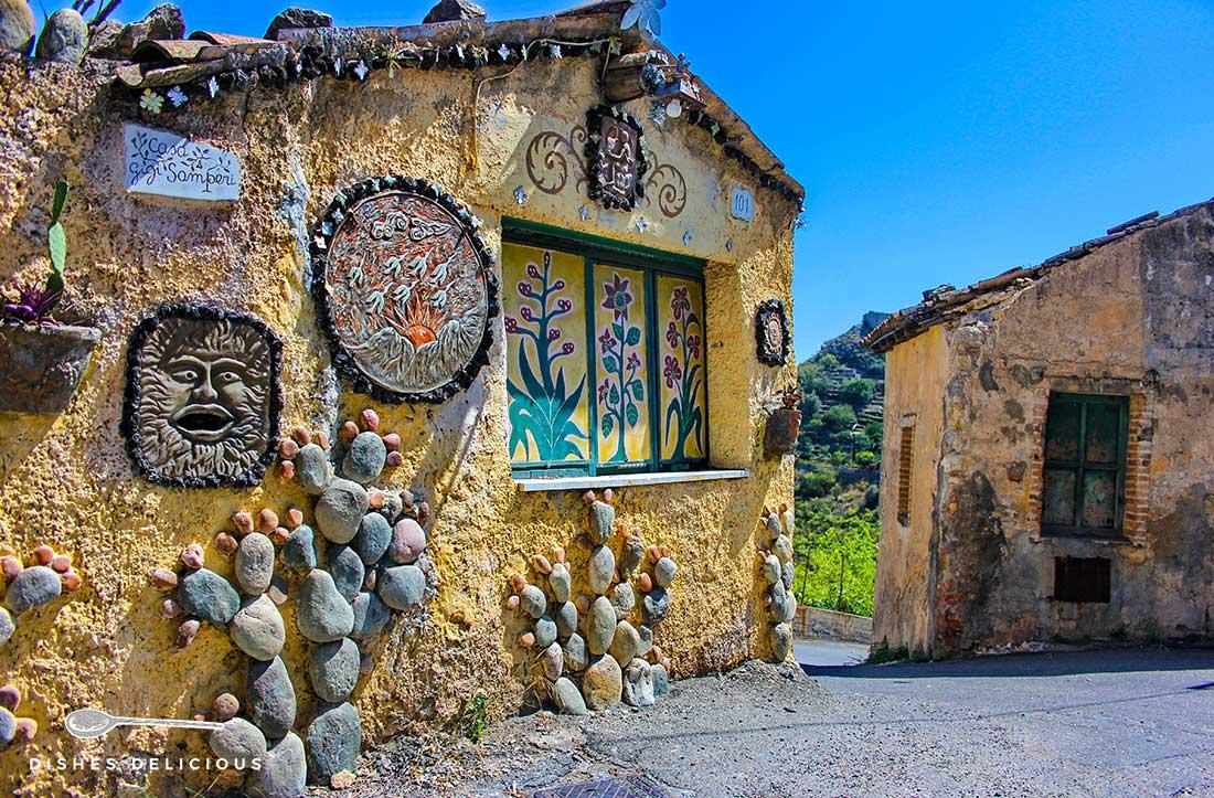 Die Casa Gigi Samperi - ein mit Steinen und Enblemen verziertes Häuschen auf dem Weg nach Castelmola