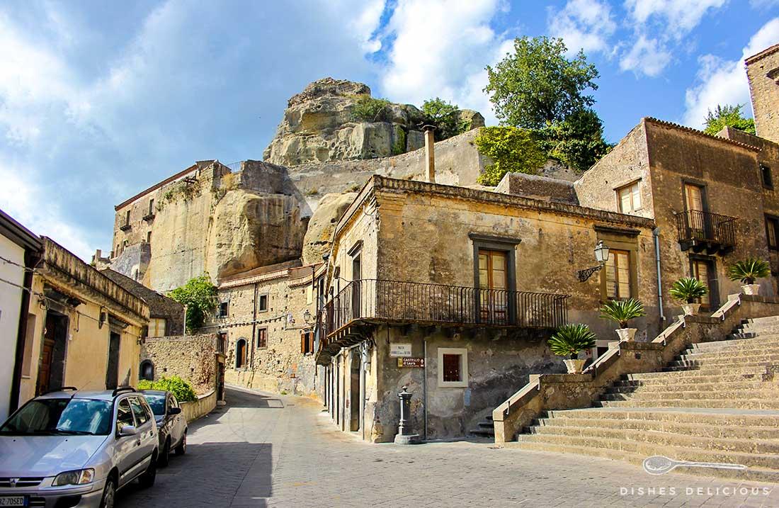 Alte Häuser in der Altstadt von Castiglione. Eine Straße führt zur Schlossruine im Hintergrund des Bildes.