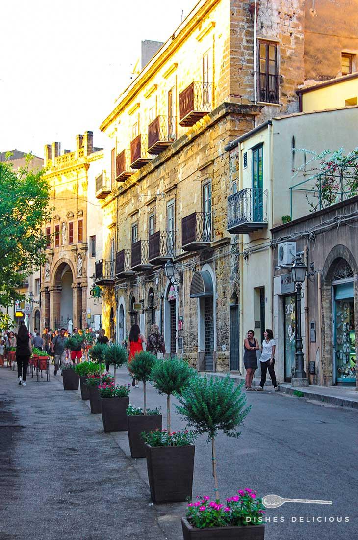 Straße in der Altstadt von Cefalù mit Geschäften, im Vordergrund stehen Blumenkübel..