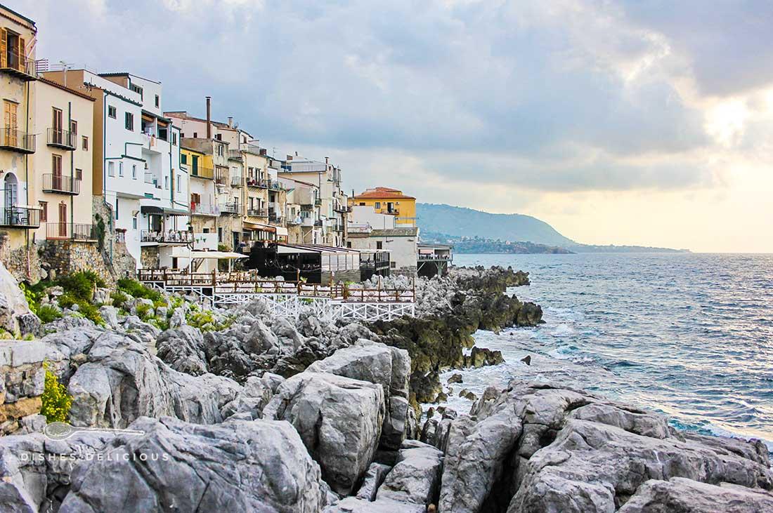 Eine Häuserreihe, die direkt am Meer steht. Ein Steinweg führt an den Häusern entlang.