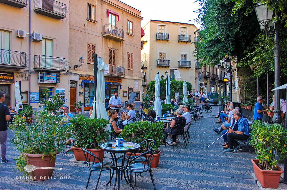 Piazza Garibaldi in Cefalù mit Tischen eines Cafès. Auf Bänken daneben sitzen alte Männer.