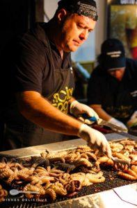 Ein Mann steht an einem Grill und grillt Octopusse.