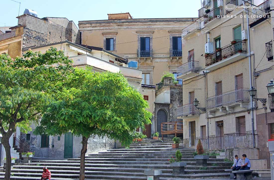 Ein kleiner Piazza mit Häusern und Bäumen. Zwei Jugendliche sitzen auf einer Bank.