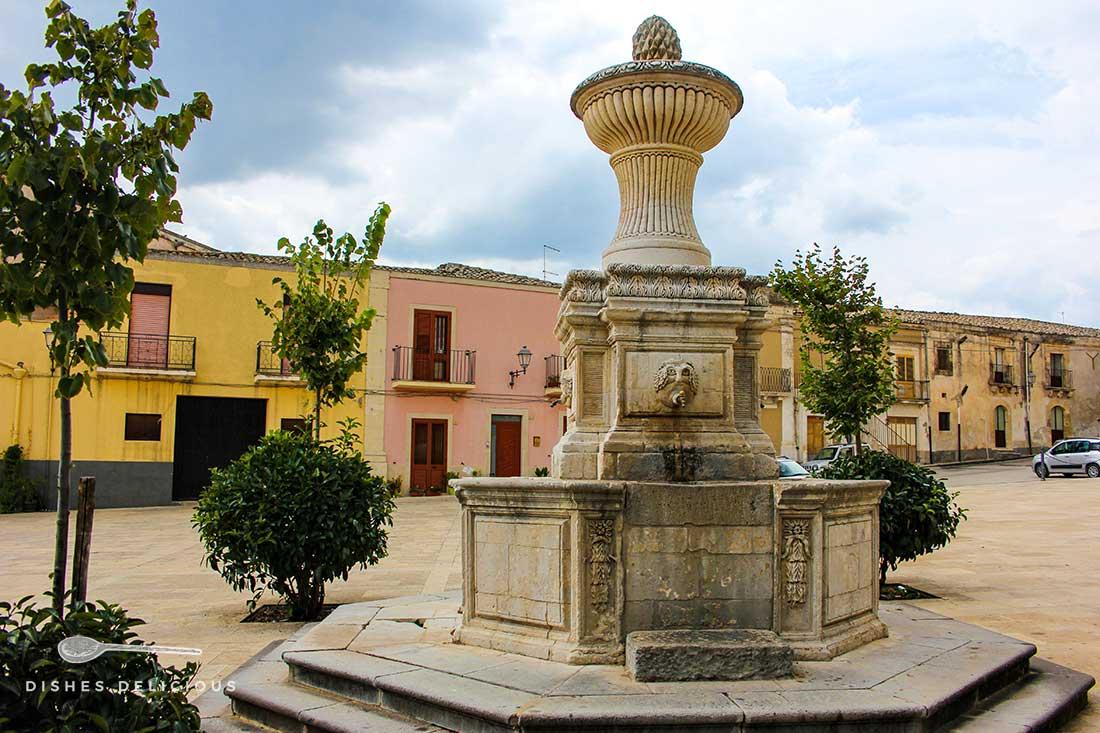 Der Brunnen Quattro Canali, umgeben von kleinen Bäumchen an der Piazza San Sebastiano in Ferla, im Hintergrund die bunten Häuser des Platzes.