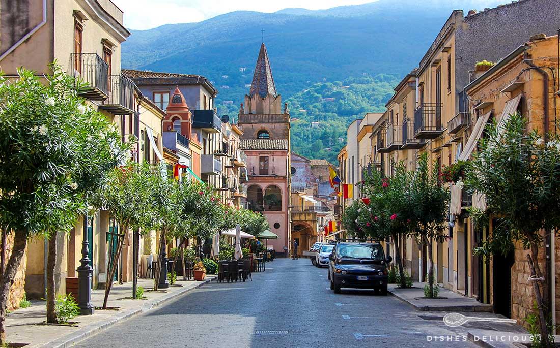 Straße zur Piazza Margherita in Castelbuono. Am Ende der Straße steht die Dorfkirche, entlang der Fahrbahn stehen kleine Bäume.