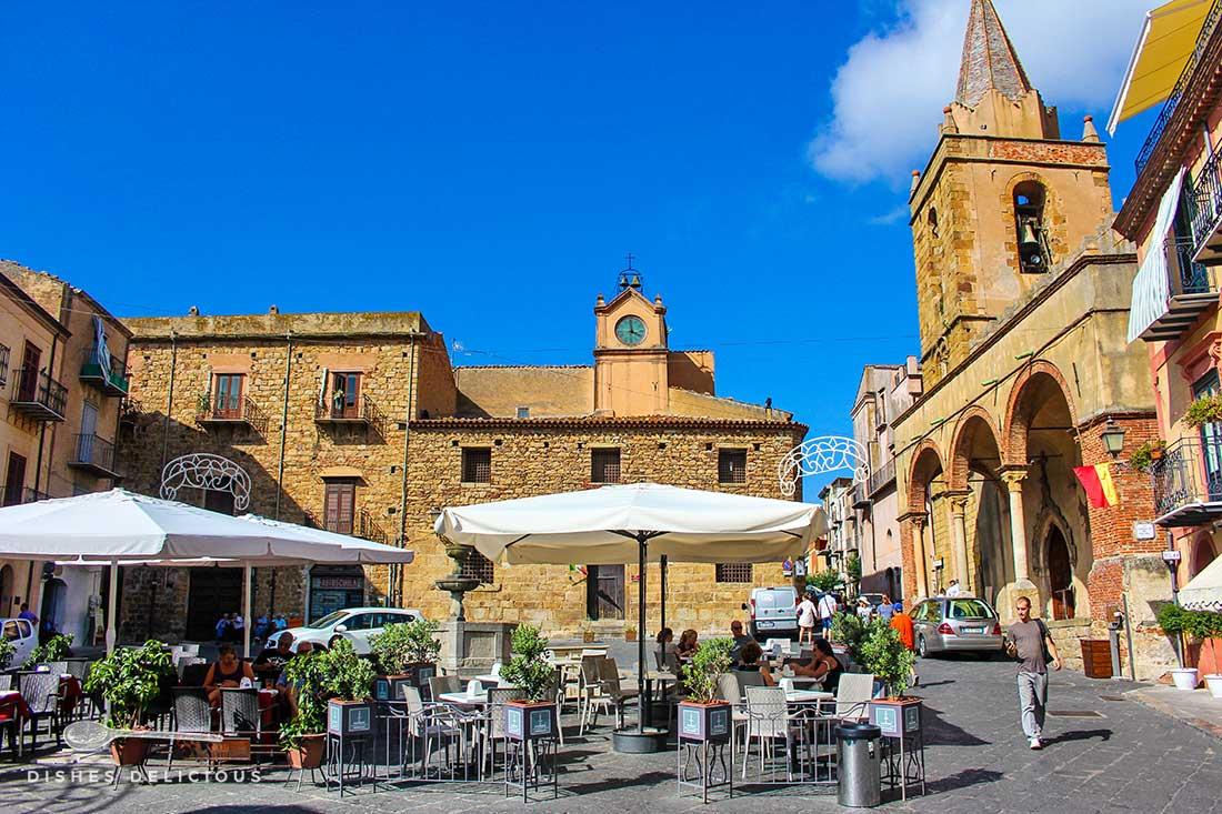 Piazza Margherita in Castelbuono: mitten auf dem Platz stehen Tische eines Cafès, rundherum alte Bauten wie die Chiesa Matrice Vecchia.