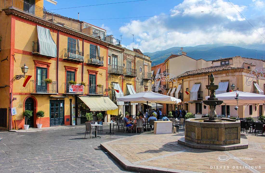 Die Piazza Margherita in Castelbuono. In der Mitte steht ein Brunnen, an dem Tische eines Cafès aufgereiht sind.