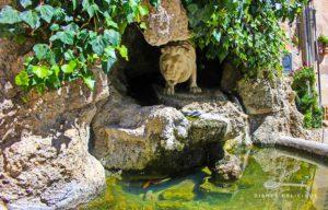 Brunnen in Gangi - er zeigt einen Mamorlöwen der aus einer Höhle ans Wasser schleicht.