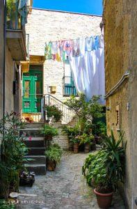 Ein kleines Haus in einer Seitengasse in Geraci. Die Gasse ist mit Blumen verziert, am Haus hängt Wäsche auf einer Leine.