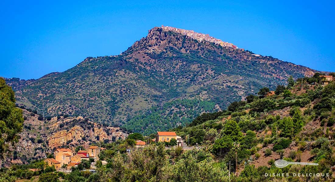 Auf einem 800 Meter hohen Berg liegt das Dorf Pollina, im Vordergrund stehen einige Häuser auf einem Hügel.