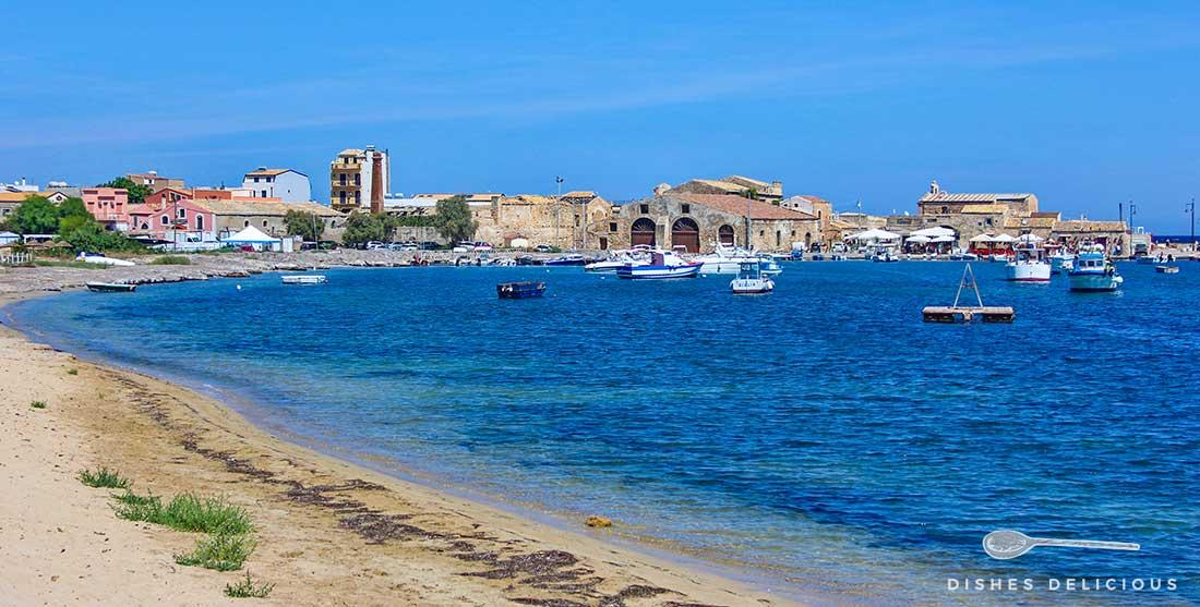 Das Bild zeigt das Fischerdorf Marzamemi mit seiner Meeresbucht. Auf dem Wasser liegen kleine Boote vor Anker.