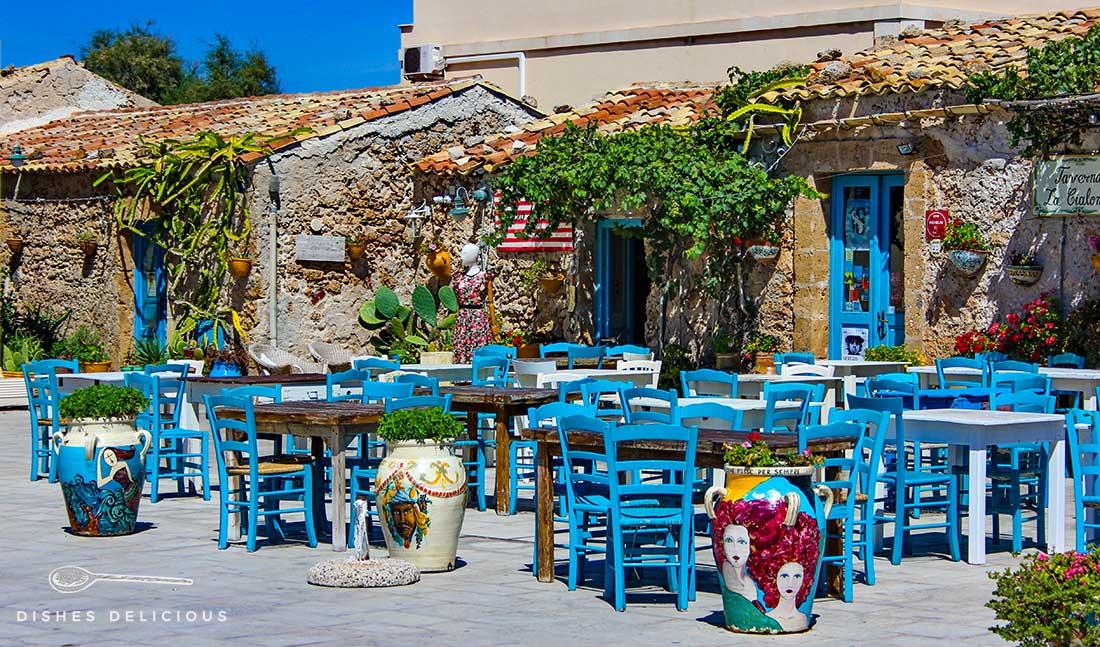 Kleine, bunt geschmückte Steinhäuschen in Marzamemi, die Trattorien beherbergen. Davor jede Menge blaue Stühle und Tische zum sitzen.