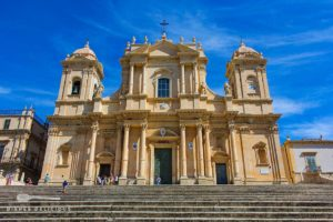 Die Eingangsfront der Kathedrale San Nicolo in Noto. Eine Treppe führt zur Kirche hinauf.