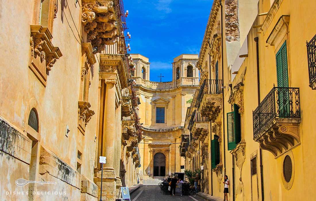Aufnahme der Via Nicolaci in Noto. Auf beiden Seiten der Straße stehen Gebäude mit stark verzierten Balkonen. Am Ende der Straße steht die Chiesa di Montevergine.