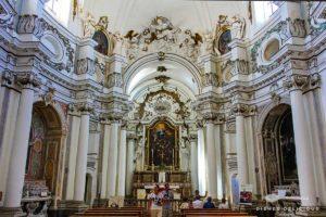 Das Innere der Santa Chiara-Kirche: stuckverzierte Säulen und viele Heiligenfiguren.