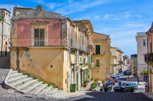 Eine Straße in Palazzolo Acreide, im Vordergrund ein altes Haus, an dem eine Treppe entlangführt.