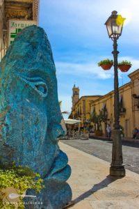 Mannshohe Gesichtsskulptur in der Fußgängerzone von Palazzolo Acreide.