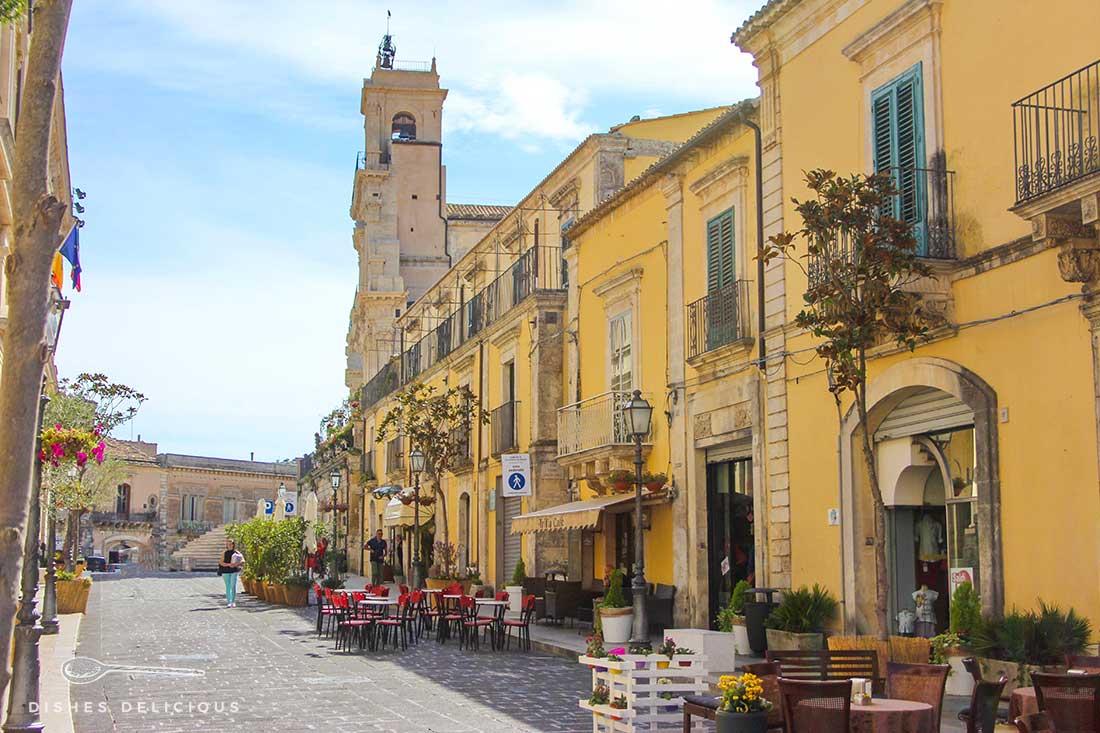 Der Corso von Palazzolo Acreide. Vor den gelben Häusern stehen Tische von Cafés. Im Hintergrund steht die San Sebstiano-Kirche.
