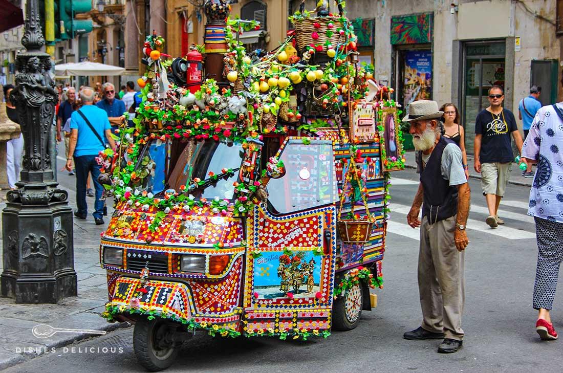 Eine bunt geschmückte Ape und Blumen und ihr betagter Besitzer an den Quattro Canti in Palermo.