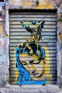 Street-Art: An die Jalousie eines Ladens ist eine Maria gesprüht, aus deren Kopf eine Ratte wächst.