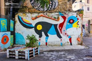 Street-Art: Ein buntes Pop-Art-Fabelwesen an einer Mauer, davor stehen bemalte Paletten, die abends als Tisch genutzt werden.