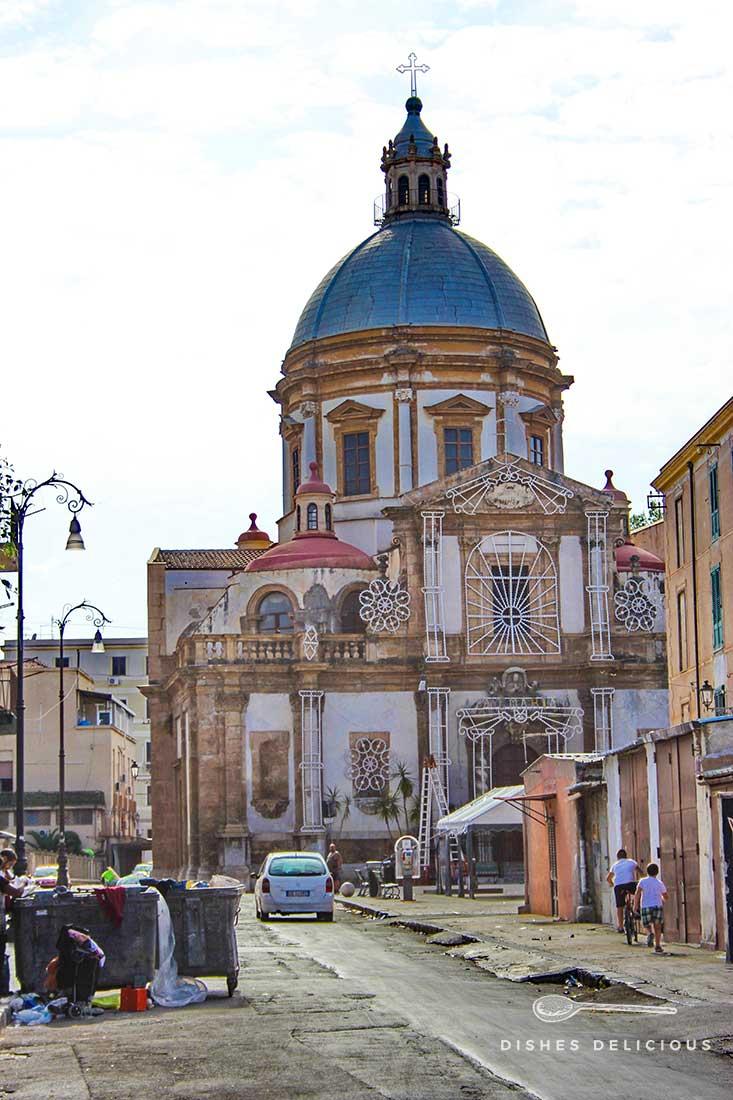 Die Kirche San Francesco Saverio. Davor zeigt sich die von Armut geprägte Seite Palermos: verfallene Häuser und offen auf der Straße stehende Müllcontainer.