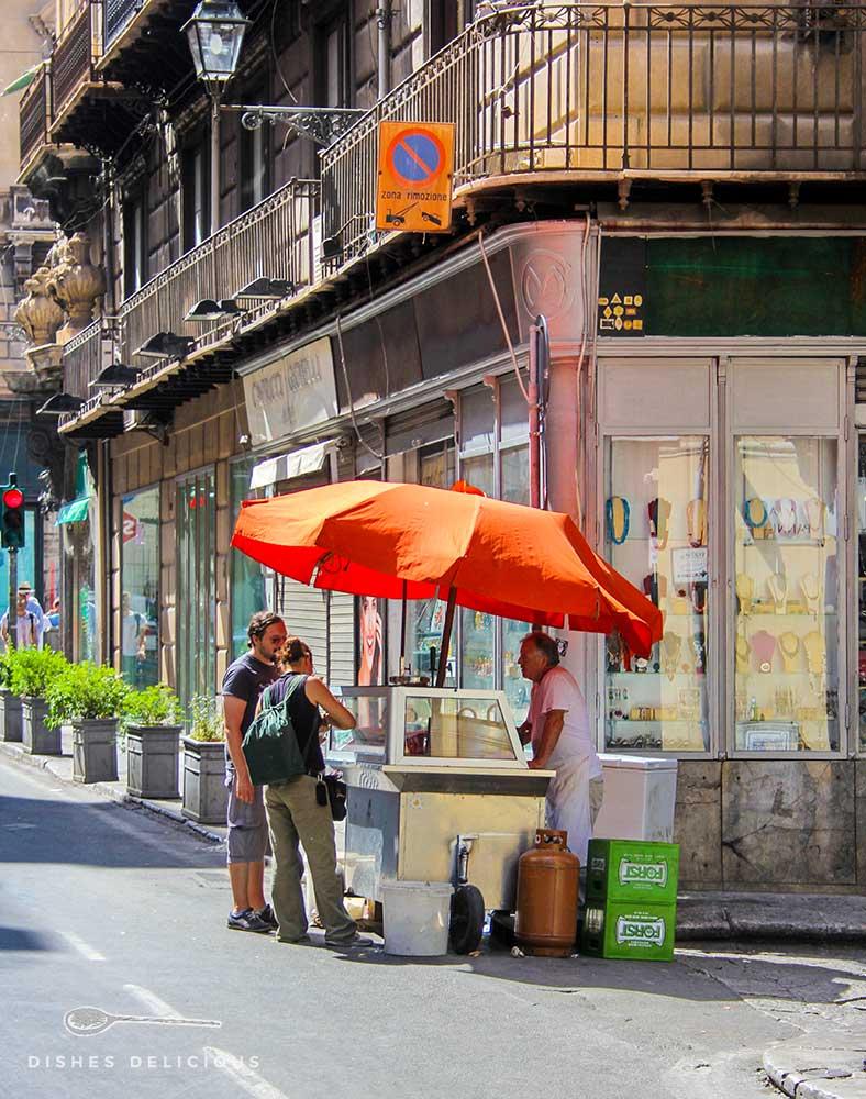 Ein mobiler Grill mit Sonnenschirm, an dem ein Street-Food-Händler zwei Touristen Milzbrötchen verkauft.