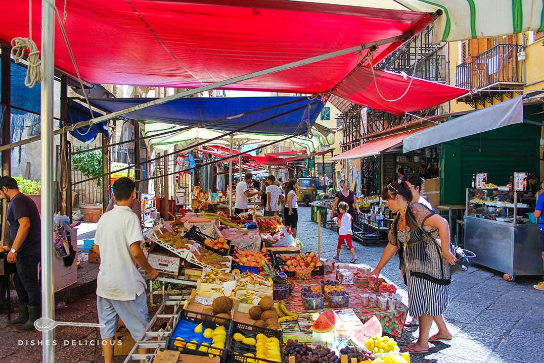 Ein Obst- und Gemüsehändler auf dem Capo-Markt in Palermo. Zwei Frauen suchen sich frisches Obst aus.