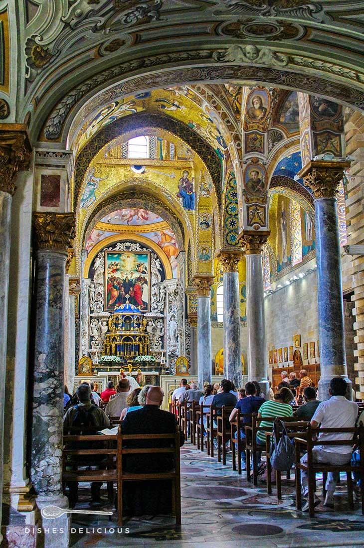 Das Innere der Admiralskirche in Palermo. Kirchgänger folgen der Messe.