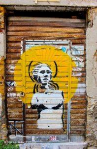 """Street-Art in Palermo: Eine Frau vor einer Sonne, daneben der Schriftzug """"Alles oder nichts"""""""