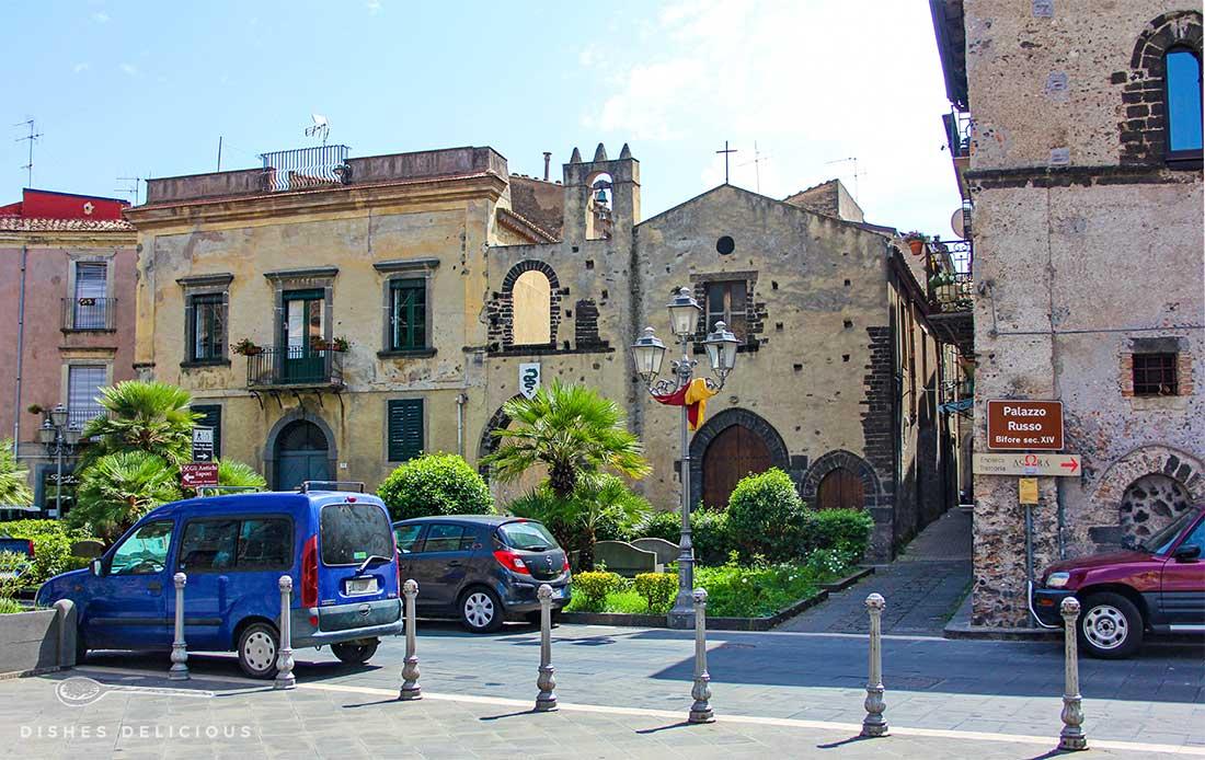 Altstadt von Randazzo: mehrere historische Gebäude, im Vordergrund parken Autos.