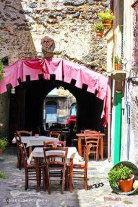 Osteria-Tische und Stühle vor einer dekorierten Unterführung in der Altstadt von Randazzo.