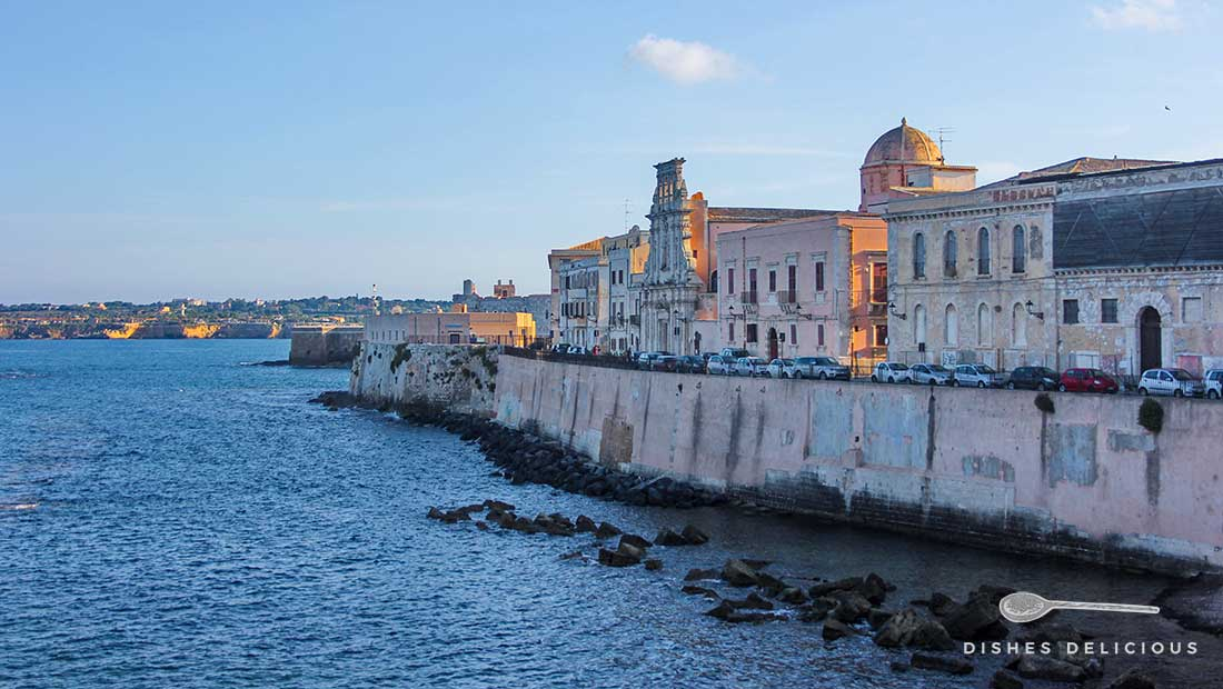 Häuser am Ufer der kleinen Insel Ortygia in Syrakus, von einer hohen Mauer vom Meer getrennt.