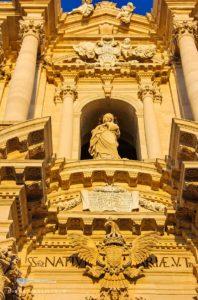 Ausschnitt aus der Barockfassade des Doms von Syrakus, in der Mitte ist zwischen Säulen eine Maria zu sehen, am Rande viele Engelsverzierungen.