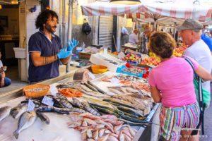 Ein Fischstand auf dem Markt von Syrakus. Der Fischverkäufer unterhält sich mit seinen Kunden.