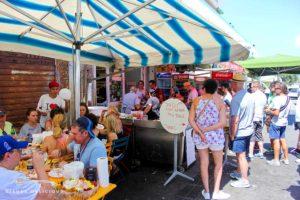 Warteschlange vor dem Caseficio Borderi. Auf der linken Seite vor der Käserei stehen Tische, an denen die Gäste Antipasti-Platten essen.