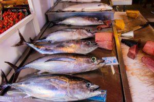 Auf einer Metallplatte liegen fünf frische Thunfische, bereit für den Verkauf auf dem Markt von Syrakus.