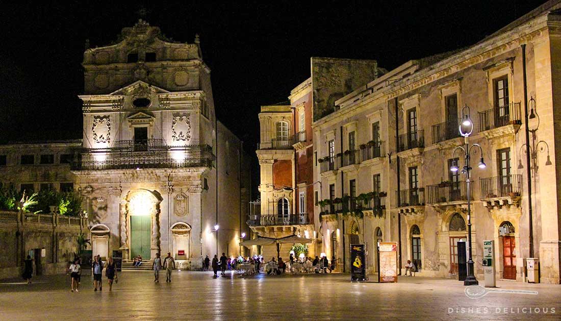 Der Domplatz von Syrakus am Abend. Die Barockkirche Santa Lucia und die Palazzi sind abendlich beleuchtet.