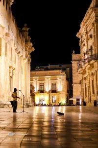 Ein Straßenmusiker singt abends auf der menschenleeren Piazza Minerva in Syrakus.