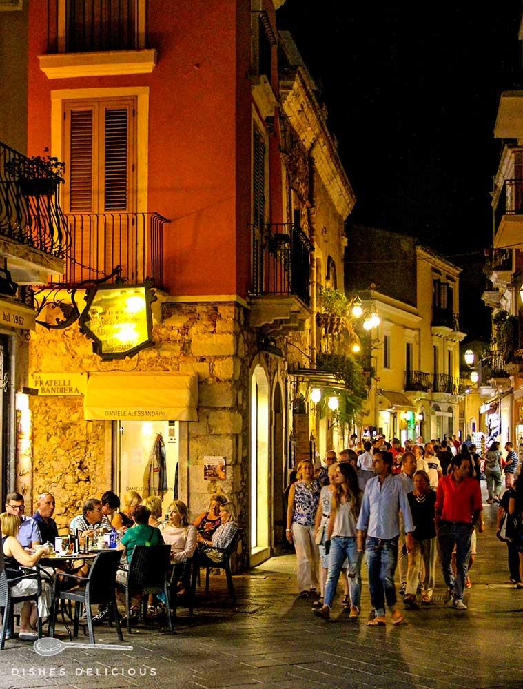 Abendliche Straßenszene auf dem Corso Umberto in Taormina. Menschen flanieren auf der Straße.