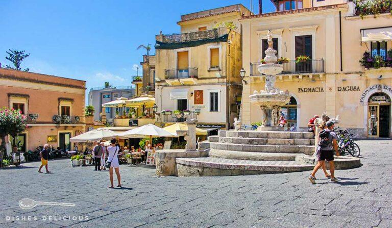 Die Piazza Duomo in Taormina. Vor einigen Cafès mit Tischen im Freien steht ein großer Brunnen.