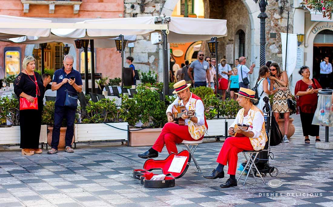 Zwei Musiker in Tracht spielen auf der Piazza IX Aprile in Taormina Gitarre.