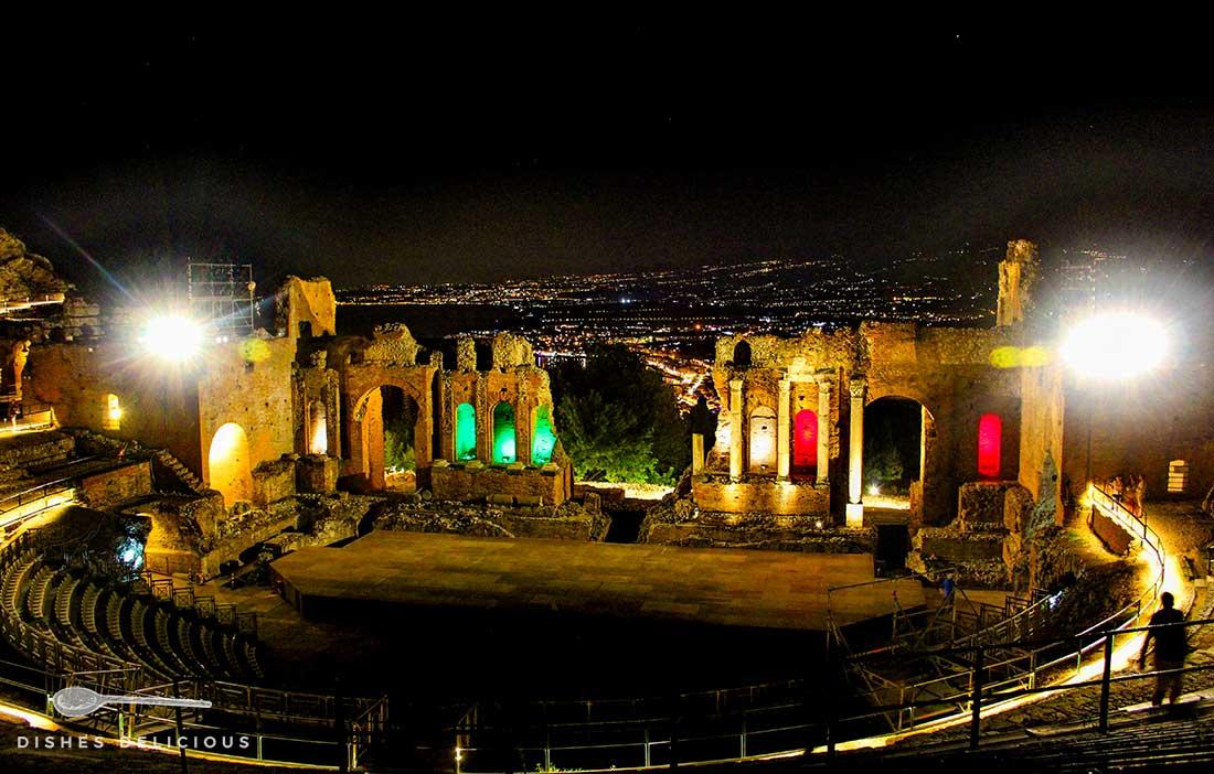 Das alte griechische Theater in Taormina bei Nacht. Im Hintergrund der beleuchtete Küstenstreifen.