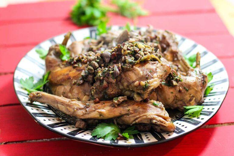 Auf einem Teller ist geschmortes Kaninchenfleisch angerichtet und mit Petersilie garniert.