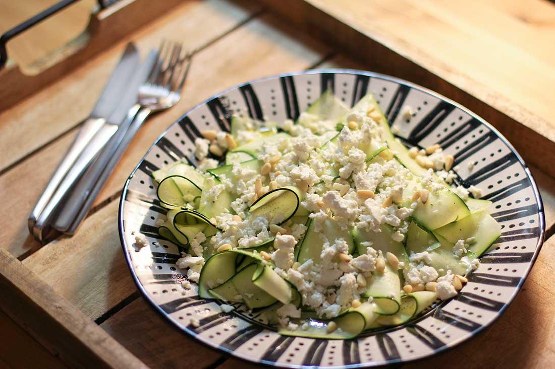 Ein Salatteller mit in Streifen geschnittenen Zucchini, garniert mit Schafskäse und Pinienkernen.